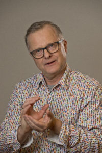 """Bilde av Nils Erik Ness i fargerik skjorte med """"talende hender""""."""