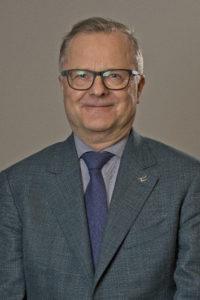 Portrettbilde av Nils Erik Ness. Smilende, kledd i dress og slips.